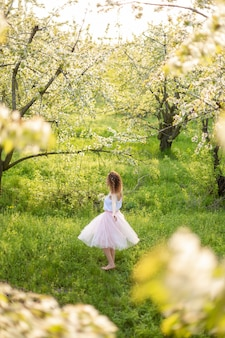 Young attractive girl walks in spring green park enjoying flowering nature