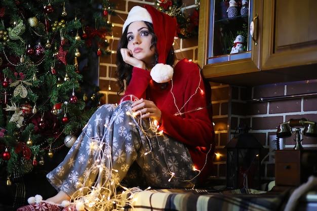 새해 나무 근처에서 따뜻한 잠옷과 침대보를 입은 젊은 매력적인 소녀. 크리스마스 분위기.
