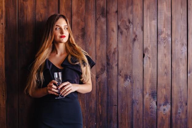 벽의 배경에 샴페인이나 와인 한 잔과 함께 젊은 매력적인 여자