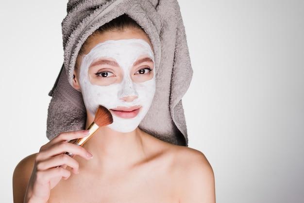 タオルnagoloveを持つ若い魅力的な女の子は、ブラシで顔に白い栄養価の高いマスクを置きます
