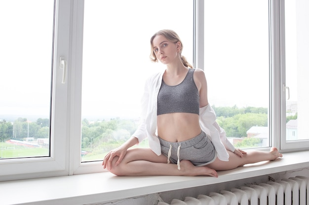 Young attractive girl with athletic body in sportswear practicing yoga, doing splits, stretching exercise on windowsill, working out indoors