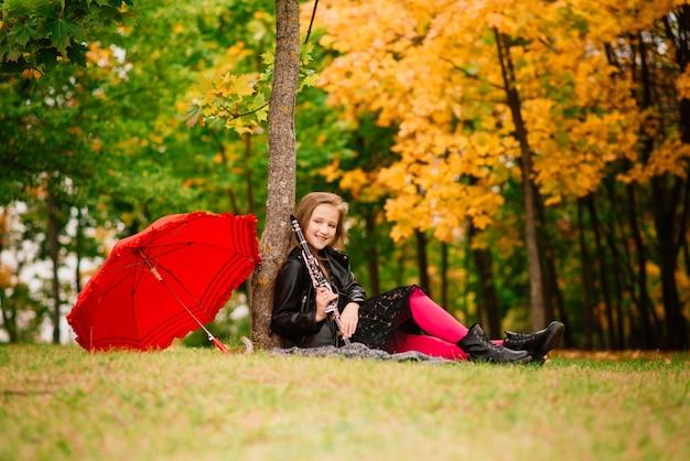 Молодая привлекательная девушка с кларнетом, черное дерево в осеннем парке