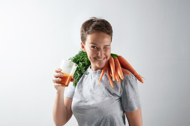 Young attractive girl with healthly perfect skin happily blinks while drinking her fresh organic carrot juice with carrot harvest on her shoulders
