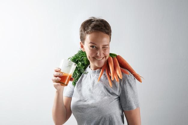 Молодая привлекательная девушка с идеальной для здоровья кожей радостно моргает, пьет свежий органический морковный сок с урожаем моркови на плечах