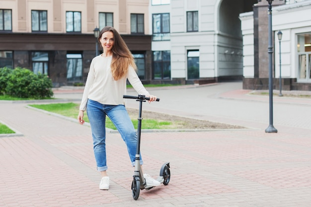 A young and attractive girl with long brown hair in a light sweater riding a scooter in a new residential complex.