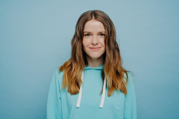 水色の背景に立っている快適なカジュアルなフード付きスウェットシャツでカメラを見ながら微笑んでいる波状のオンブルの髪型を持つ若い魅力的な女の子。ミディアムショット