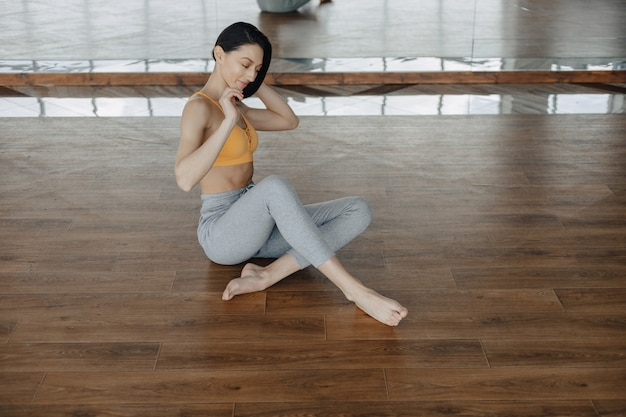 Young attractive girl on a wooden floor doing yoga, stretching and relaxing