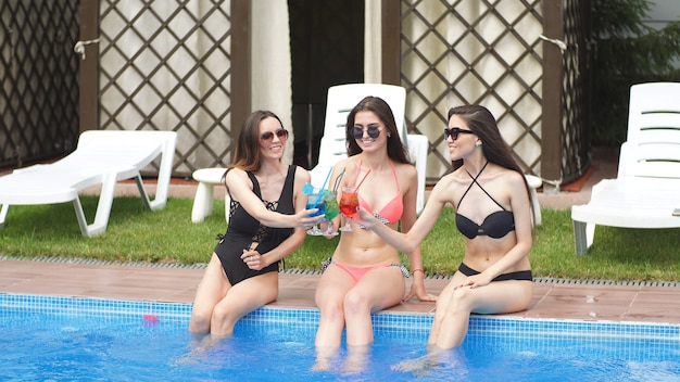Young attractive girls celebrate their birthday resting by the pool. girls drink multi-colored alcoholic cocktails lowering their legs into the water