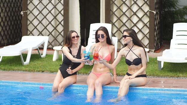 若い魅力的な女の子がプールサイドで休んで誕生日を祝います。女の子は足を水中に下げるマルチカラーのアルコールカクテルを飲む