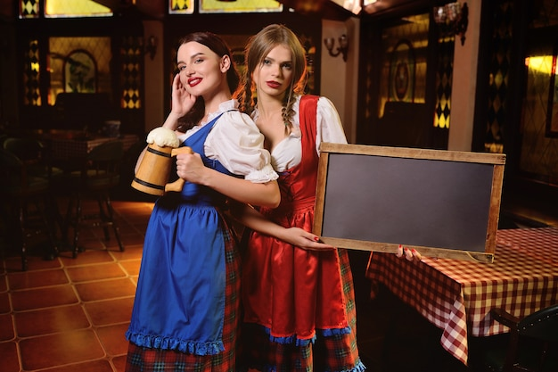 Young attractive girls in traditional bavarian clothes with chalk board and a glass of beer in their hands on the background of the pub during the oktoberfest celebration