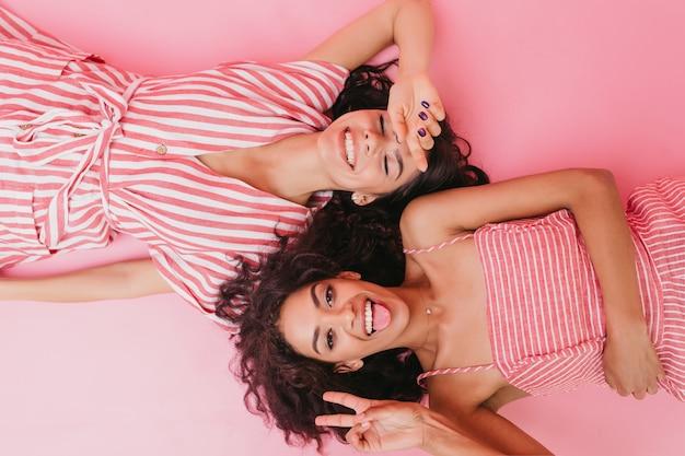 Ragazze giovani e attraenti con una bella abbronzatura e capelli ricci scuri sorridono sinceramente e mostrano un segno di pace.