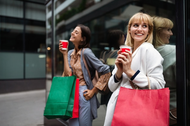 街で買い物袋とコーヒーを持っている若い魅力的な女の子。