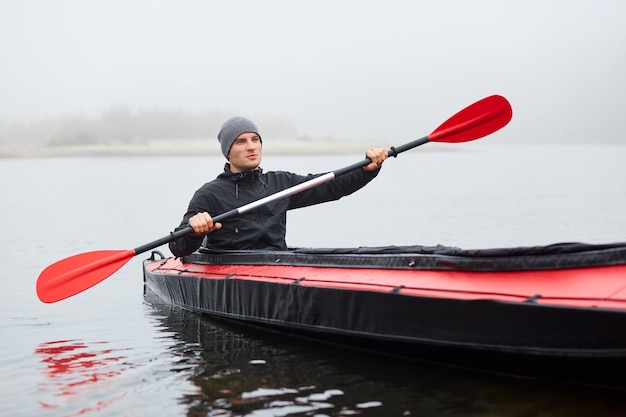 Young attractive guy having fun on kayak. kayaking on river, attractive guy in boat sailing in river, holding oar in hands