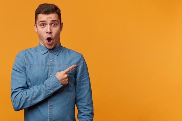 Молодой привлекательный парень в джинсовой рубашке изумлен, удивлен шокирован, показывает указательным пальцем правый верхний угол