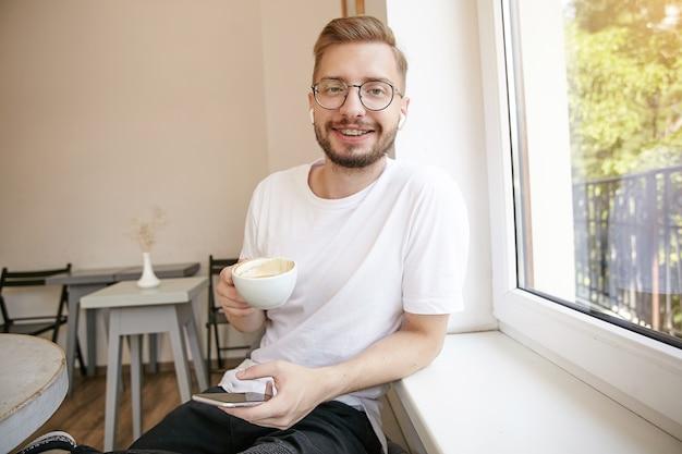 Молодой привлекательный парень в белой футболке с бородой смотрит с нежной улыбкой, сидит у окна и пьет кофе, собирается писать смс