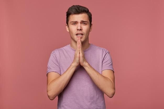 Il giovane ragazzo attraente indossa una maglietta vuota, esprime un desiderio, spera in buona fortuna e mostra pregato, sta su sfondo rosa.
