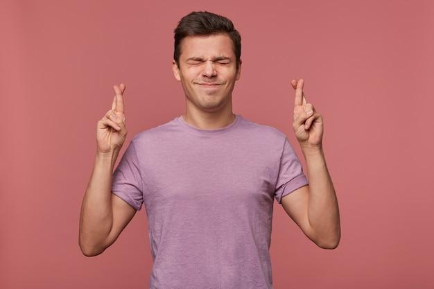 Il giovane ragazzo attraente indossa una maglietta vuota, esprime un desiderio, spera in buona fortuna con le dita incrociate, con gli occhi chiusi, isolato su sfondo rosa.