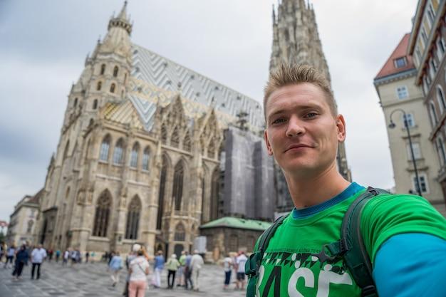 Молодой привлекательный парень с голубыми глазами, делающий селфи с огромной церковью на фоне в европе. будапешт