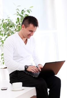 Young and attractive guy with laptop