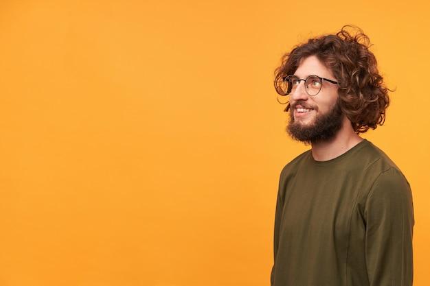 Молодой привлекательный красивый бородатый парень в очках обрадован, рад, удивлен