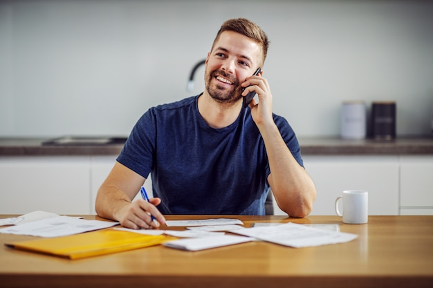 Young attractive handsome bearded smiling man calling customer service while sitting at dining table and filling in bills.