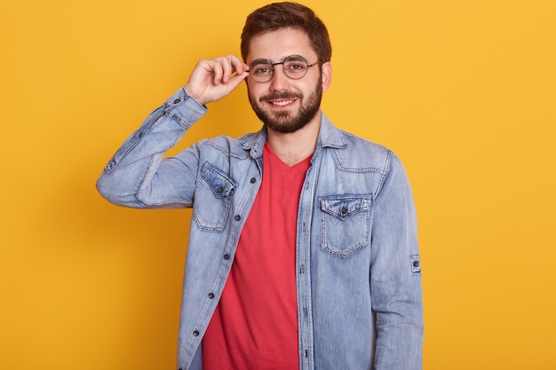 Young attractive handsome man wearing red t shirt and denim jacket standing against yellow wall and smiling, keeps hand on his spectacles