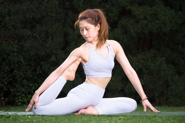 Young attractive happy asian woman in white outfit practicing her yoga balance at her home garden