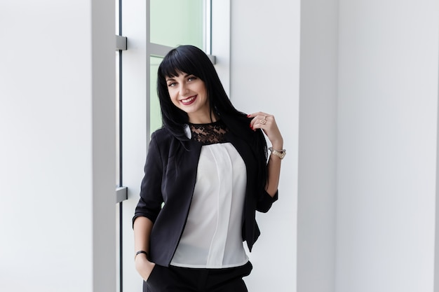 Young attractive happy brunette woman dressed in a black business suit standing near the window in office, smiling, looking at camera.