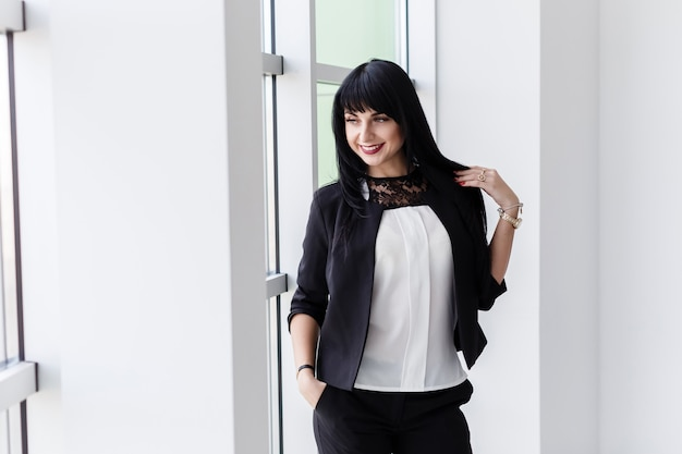 Young attractive happy brunette woman dressed in a black business suit standing near the window in a office, smiling, looking to window.