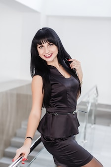 Young attractive happy brunette woman dressed in a black business suit with a short skirt is standing against the white wall in office leaning on railing, smiling, looking to camera.