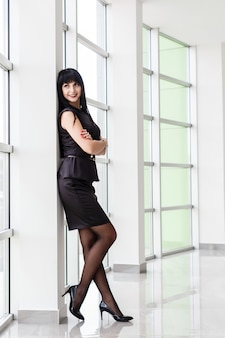 Young attractive happy brunette woman dressed in a black business suit with a short skirt is standing near the window in a white office, smiling.