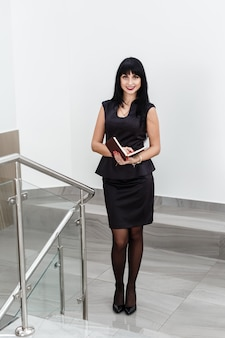 Young attractive happy brunette woman dressed in a black business suit working with a notebook, standing in a office, smiling.