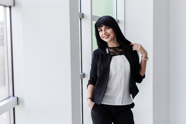 Young attractive happy brunette woman dressed in a black business suit