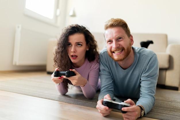 Молодая привлекательная счастливая пара, играя в видеоигры дома