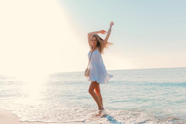 Молодая привлекательная счастливая женщина танцует поворачиваясь на берегу моря в солнечном летнем стиле моды в белом платье на каникулах