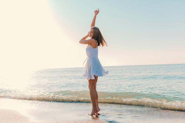 Молодая привлекательная счастливая женщина танцует, поворачиваясь на берегу моря в солнечном летнем стиле моды в белом платье