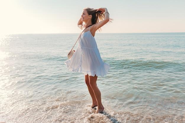 Молодая привлекательная счастливая женщина танцует, оборачиваясь на берегу моря в солнечном летнем стиле моды