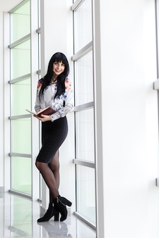 Young attractive happy woman standing near the window