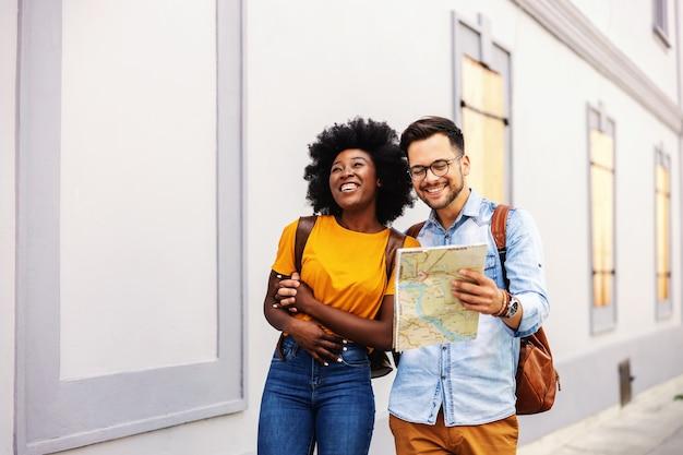 Пара молодых привлекательных битник мультикультурного ходить в центр города и глядя на карту.