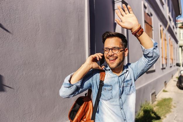 屋外に立って、ガールフレンドと電話で会話し、友人に手を振っている若い魅力的なヒップスター。