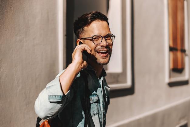 屋外に立って、彼のガールフレンドと電話で会話している若い魅力的なヒップスター。