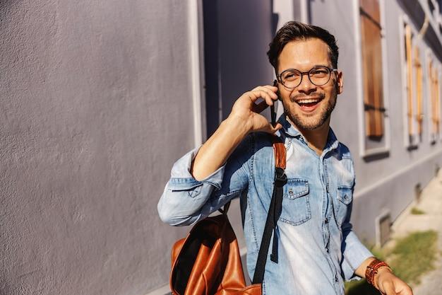 屋外に立って電話で会話する若い魅力的なヒップスター