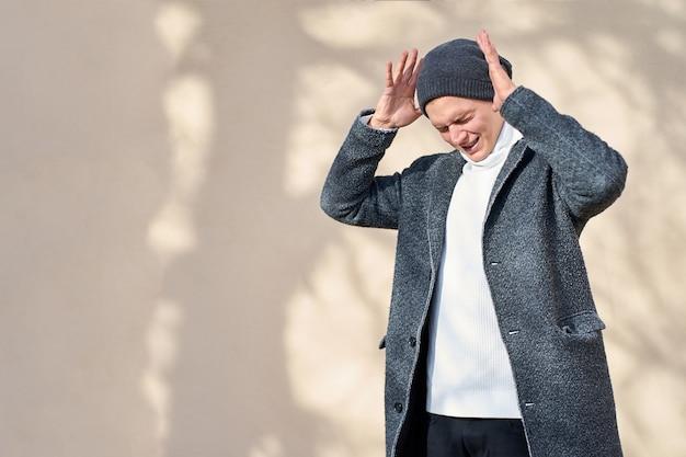회색 코트, 흰색 스웨터와 검은 색 청바지를 입고 닫힌 눈을 가진 젊은 매력적인 힙 스터 유행 남자