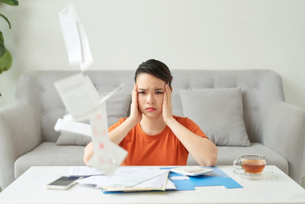 Young attractive housewife upset by utility bills, she counts family budget and pays bills online, being at home