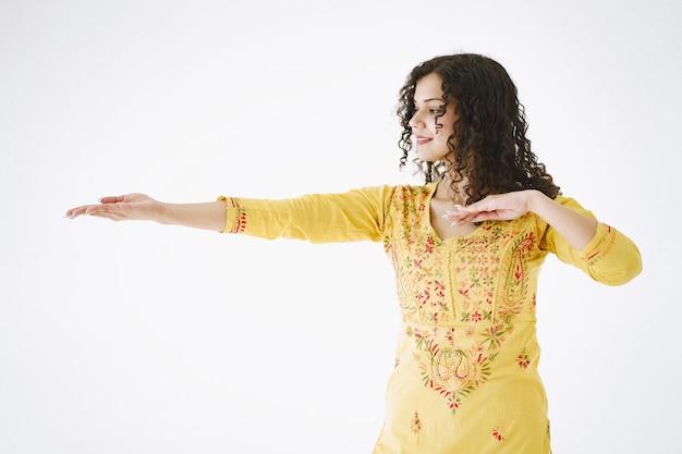 Молодая привлекательная индийская женщина в традиционной одежде. женщина танцует на белом фоне.