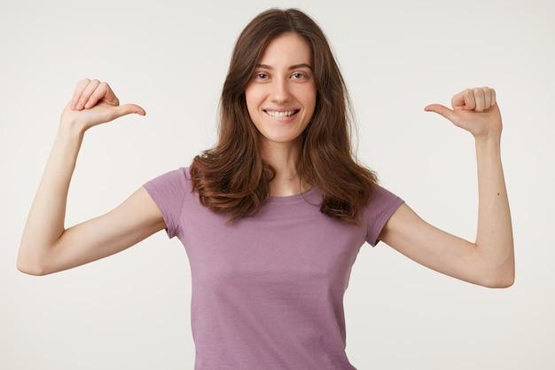 젊은 매력적인 영감을받은 여성이 열정적으로 엄지 손가락으로 자신을 보여주고, 그녀의 승리를 축하합니다.