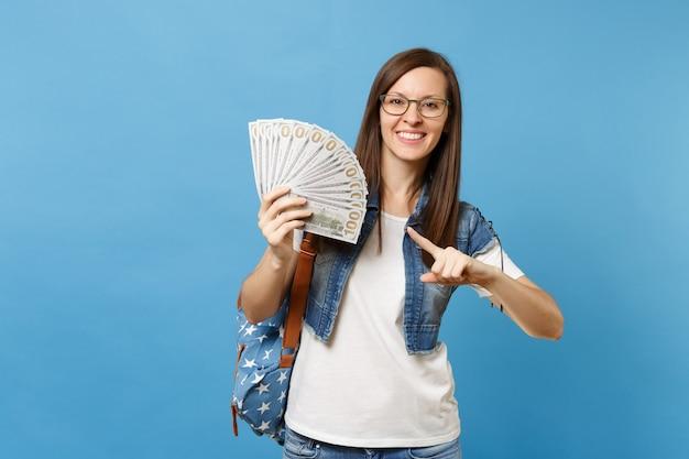 Молодой привлекательный радостный студент женщины в очках с рюкзаком, указывая указательным пальцем на пачку много долларов, наличные деньги, изолированные на синем фоне. обучение в средней школе университетского колледжа.