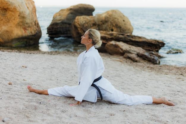 Молодая привлекательная женщина каратэ в белом кимоно с черным поясом сидит в шпагате на песке на диком пляже с камнями