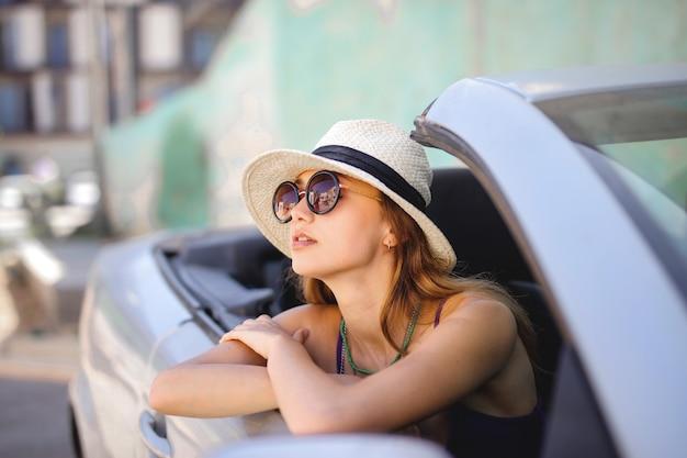 Молодая привлекательная дама в белой шляпе и солнечных очках смотрит из кабриолета