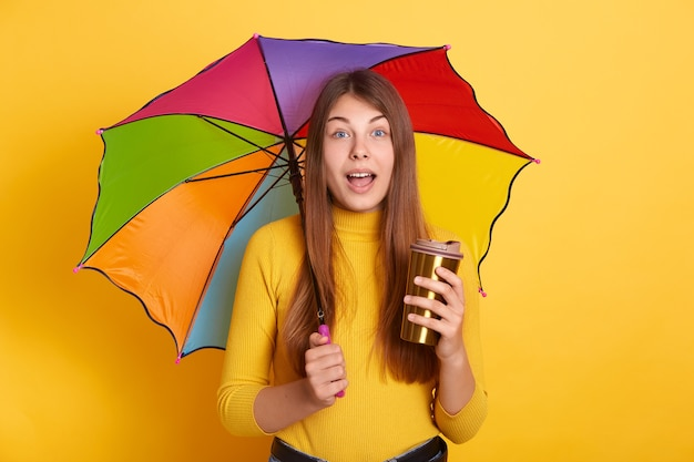 Young attractive lady with astonished facial expression posing with multicolored umbrella and coffee to go, stands with opened mouth
